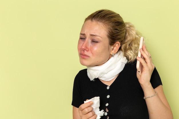 Vue de face jeune femme se sentant très malade et malade de parler au téléphone sur le plancher vert maladie médecine maladie