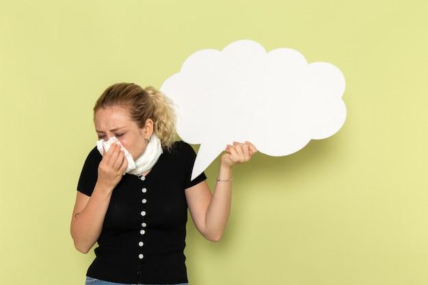 Vue de face jeune femme se sentir très malade et malade tenant un énorme panneau blanc sur le mur vert clair maladie médecine médecine maladie fille