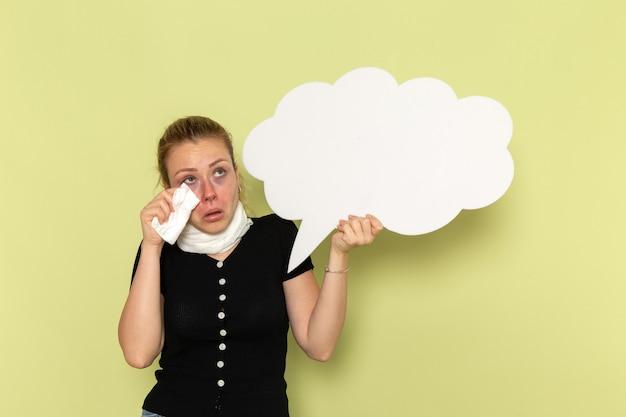 Vue de face jeune femme se sentir très malade et malade tenant un énorme panneau blanc sur le mur vert fille maladie médecine santé maladie