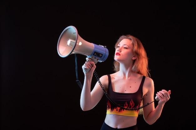 Une vue de face jeune femme séduisante en chemise de feu et pantalon noir à l'aide d'un mégaphone sur le volume de fond noir fort