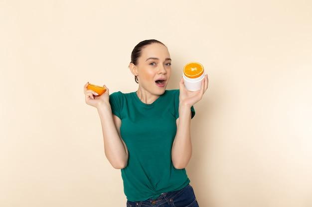 Vue de face jeune femme séduisante en chemise vert foncé tenant des anneaux orange sur beige