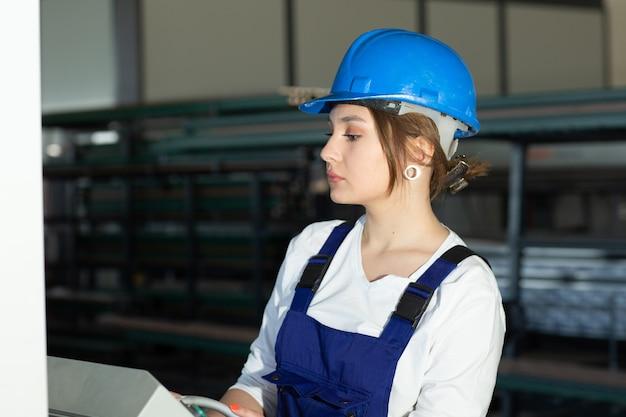 Une vue de face jeune femme séduisante en combinaison de construction bleue et casque contrôlant les machines dans le hangar travaillant pendant la construction de l'architecture des bâtiments pendant la journée