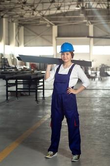 Une vue de face jeune femme séduisante en costume bleu et casque de travail tenant une chose métallique lourde pendant la construction de l'architecture des bâtiments pendant la journée