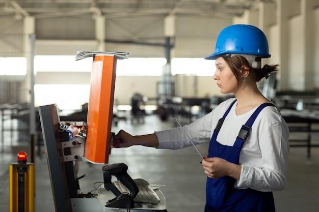 Une vue de face jeune femme séduisante en costume de construction bleu et casque contrôlant les machines dans le hangar pendant la construction de l'architecture des bâtiments de jour