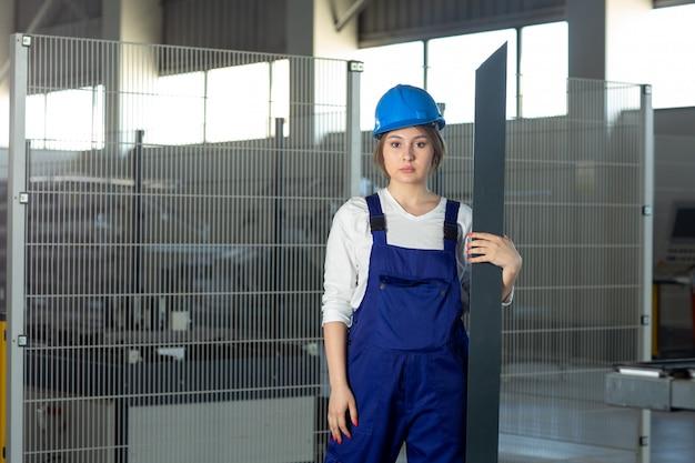 Une vue de face jeune femme séduisante en costume de construction bleu et casque de travail tenant des détails métalliques lourds pendant la construction de l'architecture des bâtiments pendant la journée