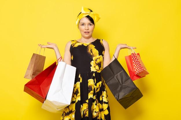 Une vue de face jeune femme séduisante en fleur jaune-noir conçu robe avec bandage jaune sur la tête posant tenant des colis sur le jaune