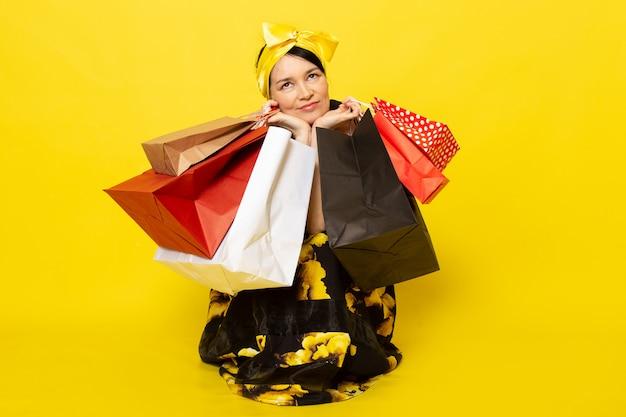 Une vue de face jeune femme séduisante en fleur jaune-noir conçu robe avec bandage jaune sur la tête smiling holding shopping packages sur le jaune