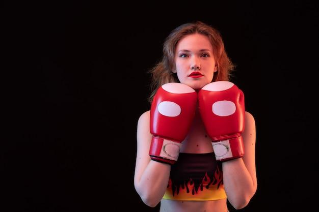 Une vue de face jeune femme séduisante en gants de boxe rouge chemise de feu sur le fond noir de la formation de boxe sport