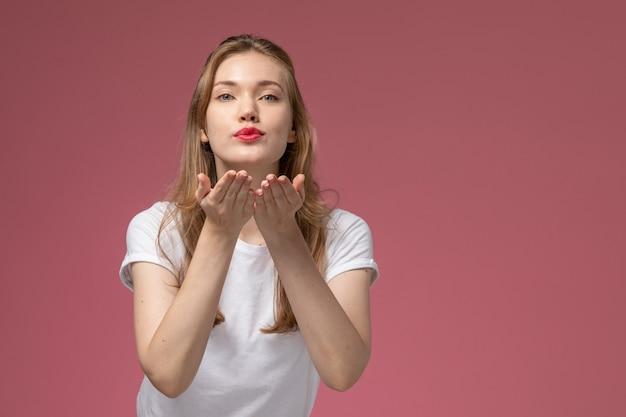 Vue de face jeune femme séduisante en t-shirt blanc envoi de bisous d'air sur un mur rose foncé couleur modèle femme jeune fille
