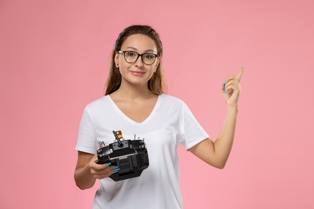 Vue de face jeune femme séduisante en t-shirt blanc avec expression mécontente tenant la télécommande sur le bureau rose