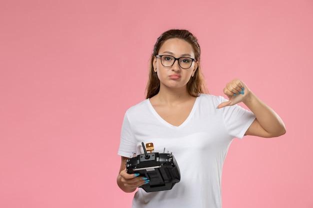 Vue de face jeune femme séduisante en t-shirt blanc avec une expression mécontente tenant la télécommande sur le fond rose