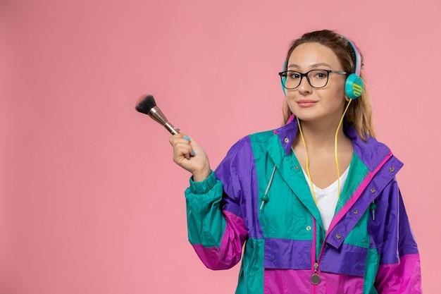 Vue de face jeune femme séduisante en t-shirt blanc manteau coloré écouter de la musique avec des écouteurs sur le fond rose pose la beauté du modèle