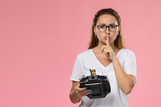 Vue de face jeune femme séduisante en t-shirt blanc montrant le signe du silence et tenant la télécommande sur le fond rose