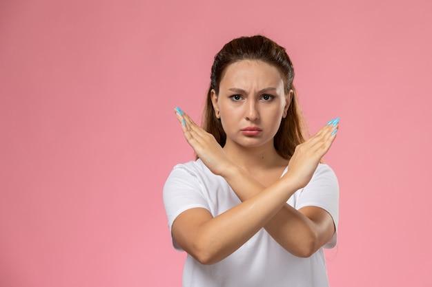Vue de face jeune femme séduisante en t-shirt blanc montrant le signe d'interdiction avec une expression mécontente sur le fond rose
