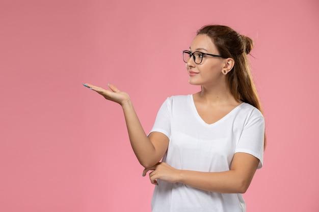 Vue de face jeune femme séduisante en t-shirt blanc posant et smi sur fond rose