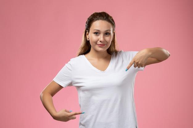 Vue de face jeune femme séduisante en t-shirt blanc posant avec sourire sur fond rose