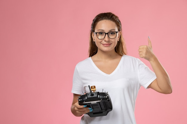 Vue de face jeune femme séduisante en t-shirt blanc smi et tenant la télécommande sur le fond rose