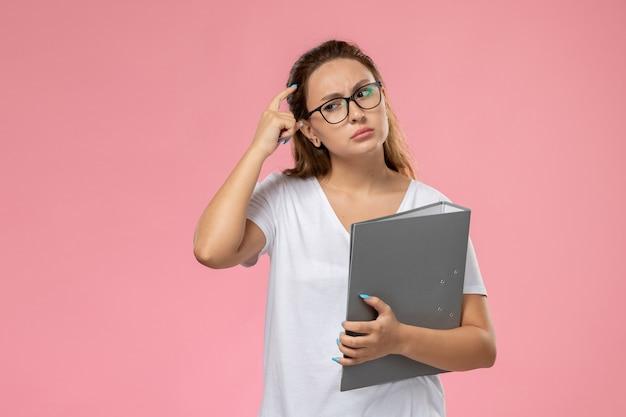 Vue de face jeune femme séduisante en t-shirt blanc tenant un fichier gris et pensant sur le fond rose