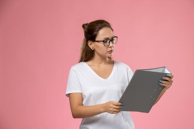 Vue de face jeune femme séduisante en t-shirt blanc tenant et lisant le fichier gris sur fond rose