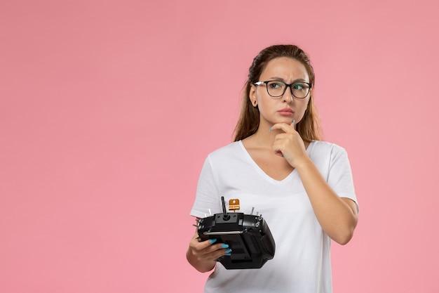 Vue de face jeune femme séduisante en t-shirt blanc tenant la télécommande avec l'expression de la pensée sur le fond rose