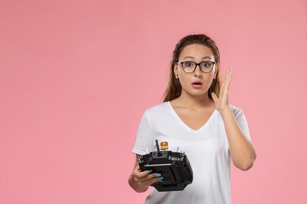 Vue de face jeune femme séduisante en t-shirt blanc tenant la télécommande sur le fond rose