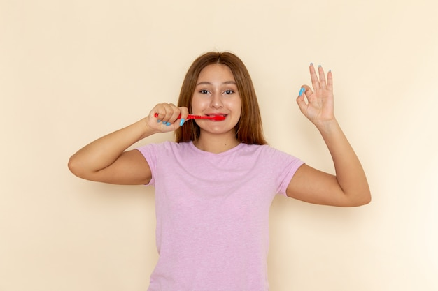 Vue de face jeune femme séduisante en t-shirt rose et blue-jeans nettoyant ses dents avec sourire