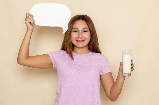 Vue de face jeune femme séduisante en t-shirt rose et blue-jeans tenant du lait et signe