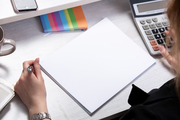 Une vue de face jeune femme séduisante travaillant avec des documents en face de la table avec des calculatrices tasse téléphone fond clair travailler les technologies de l'entreprise