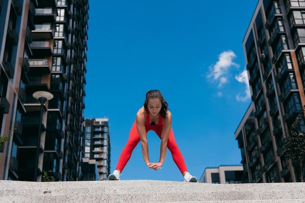 Vue de face de la jeune femme séduisante en vêtements de sport rouge pratiquant vers l'avant et l'étirement des ischio-jambiers