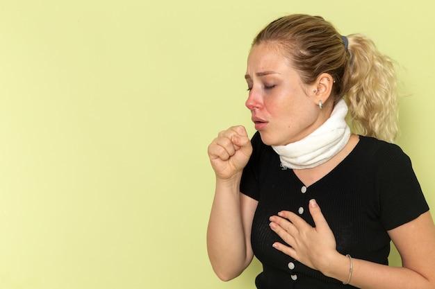 Vue de face jeune femme avec une serviette blanche autour de sa gorge se sentir très malade et mal toux sur le bureau vert maladie maladie couleur femme