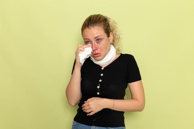 Vue de face jeune femme avec une serviette blanche autour de sa gorge se sentir très malade et malade sur mur vert clair maladie maladie femme fille santé