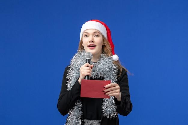 Vue de face d'une jeune femme en soirée karaoké avec enveloppe sur le mur bleu