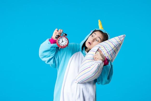 Vue de face jeune femme en soirée pyjama tenant des horloges et essayant de s'endormir sur un oreiller sur fond bleu lit rêve sommeil tard repos cauchemar amis amusement bâillement