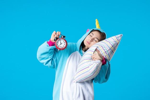 Vue de face jeune femme en soirée pyjama tenant des horloges et essayant de s'endormir sur un oreiller sur fond bleu lit rêve sommeil tard repos cauchemar nuit amis amusement bâillement