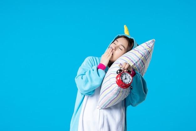 Vue de face jeune femme en soirée pyjama tenant des horloges et essayant de s'endormir sur un oreiller sur fond bleu lit rêve sommeil tard repos cauchemar nuit amusement bâillement