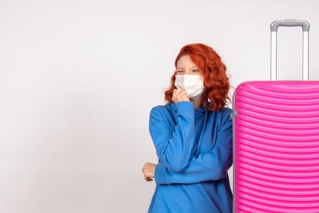 Vue de face de la jeune femme avec son sac rose en masque sur mur blanc