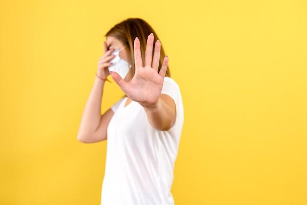 Vue de face de la jeune femme a souligné sur le mur jaune