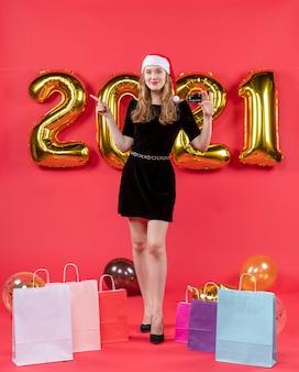 Vue de face jeune femme souriante dans des sacs de robe noire sur des ballons au sol sur rouge