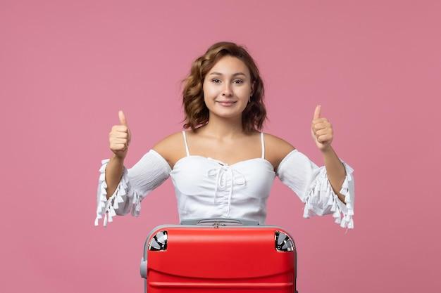 Vue de face d'une jeune femme souriante avec son sac rouge sur un mur rose