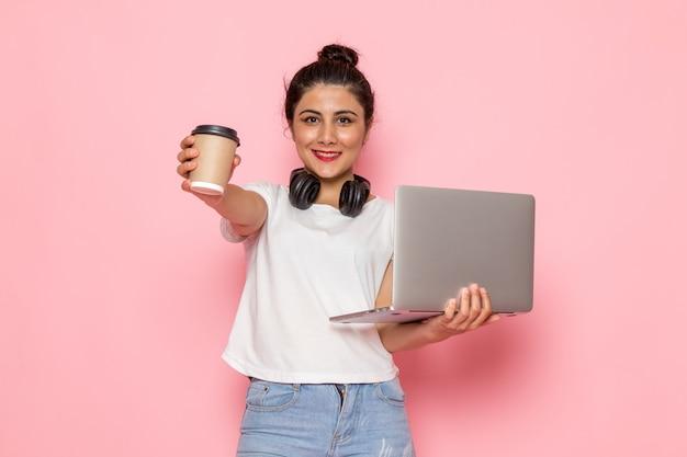 Une vue de face jeune femme en t-shirt blanc et blue-jeans tenant un ordinateur portable et une tasse de café