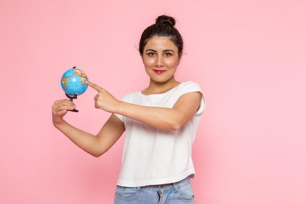 Une vue de face jeune femme en t-shirt blanc et blue-jeans tenant petit globe