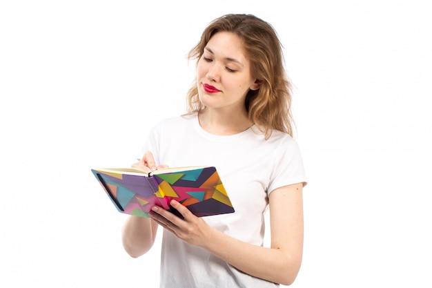 Une vue de face jeune femme en t-shirt blanc, écrire des notes sur le blanc