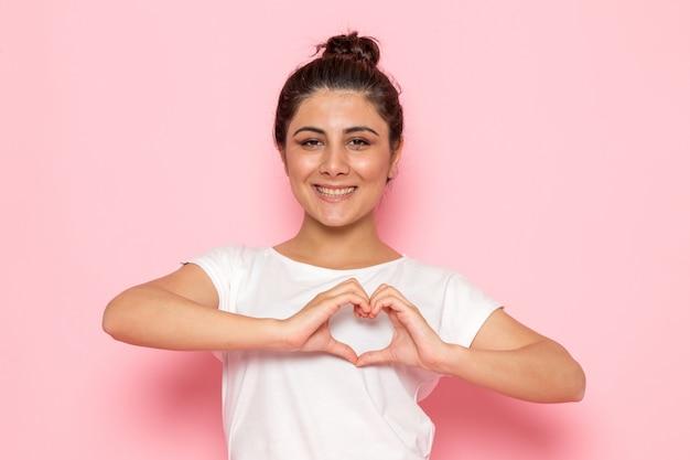 Une vue de face jeune femme en t-shirt blanc et jean bleu posant et montrant la forme de coeur