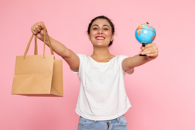 Une vue de face jeune femme en t-shirt blanc et jean bleu posant avec sourire tenant petit globe et paquet