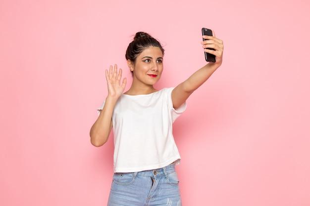 Une vue de face jeune femme en t-shirt blanc et jean bleu prenant un selfie