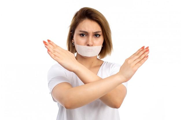Une vue de face jeune femme en t-shirt blanc et jean noir portant un bandage blanc autour de sa bouche montrant le signe d'interdiction sur le blanc