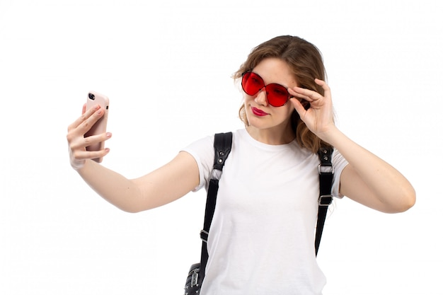 Une vue de face jeune femme en t-shirt blanc lunettes de soleil rouges sac noir souriant prenant selfie sur le blanc