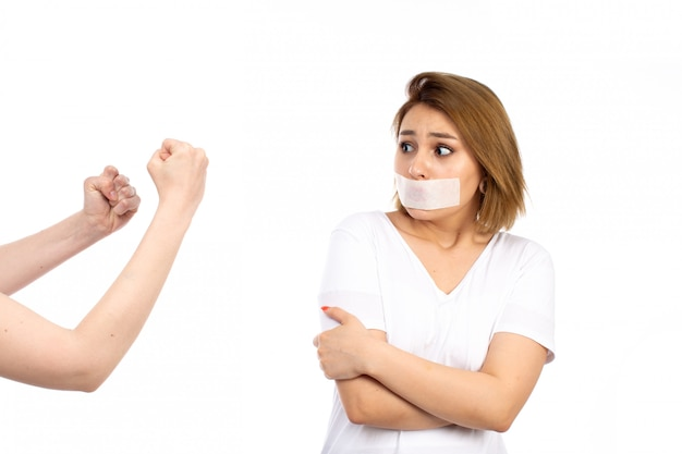 Une vue de face jeune femme en t-shirt blanc portant un bandage blanc autour de sa bouche plaider coupable expression de peur sur le blanc