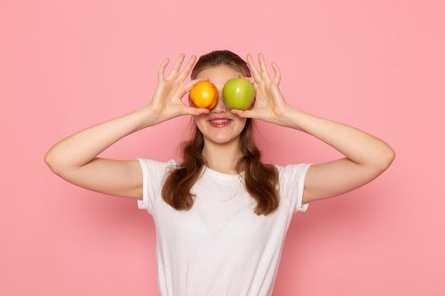 Vue de face de la jeune femme en t-shirt blanc tenant pomme verte fraîche et pêche