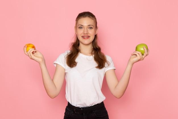 Vue de face de la jeune femme en t-shirt blanc tenant une pomme verte fraîche et souriant sur un mur rose clair